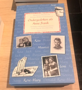 "A book with the title, ""Ondergedoken als Anne Frank: tales of Jewish children in hiding.""  The cover features black and white photos of several children."
